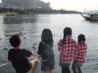 船上デッキでカモメにえさをあたえる子どもたち