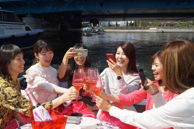 乾杯している様子を写真に撮る女性たち