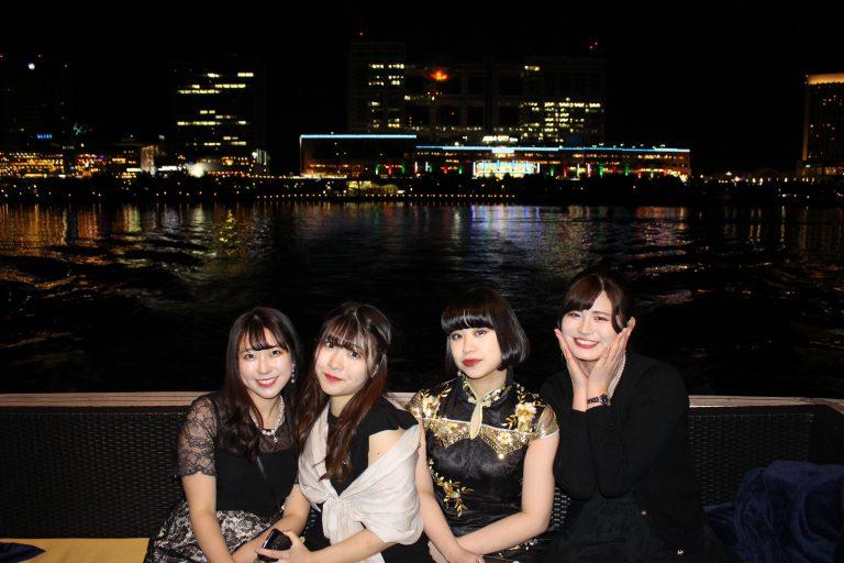 夜景をバックにクルーザーで写真を撮る女性たち