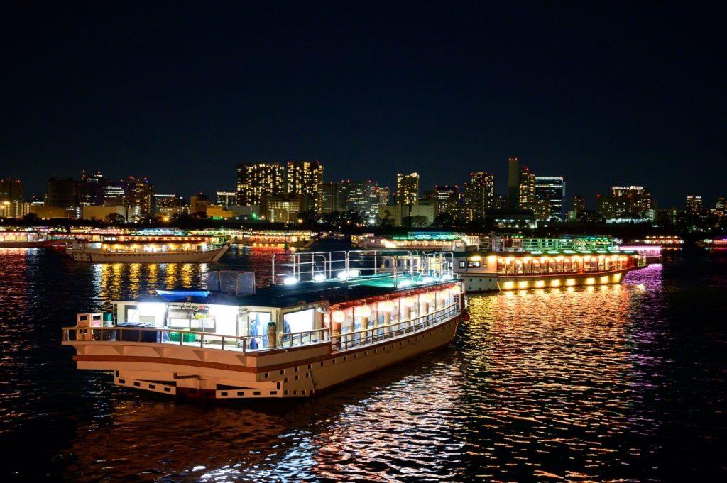 夜の海に浮かぶ数隻の屋形船
