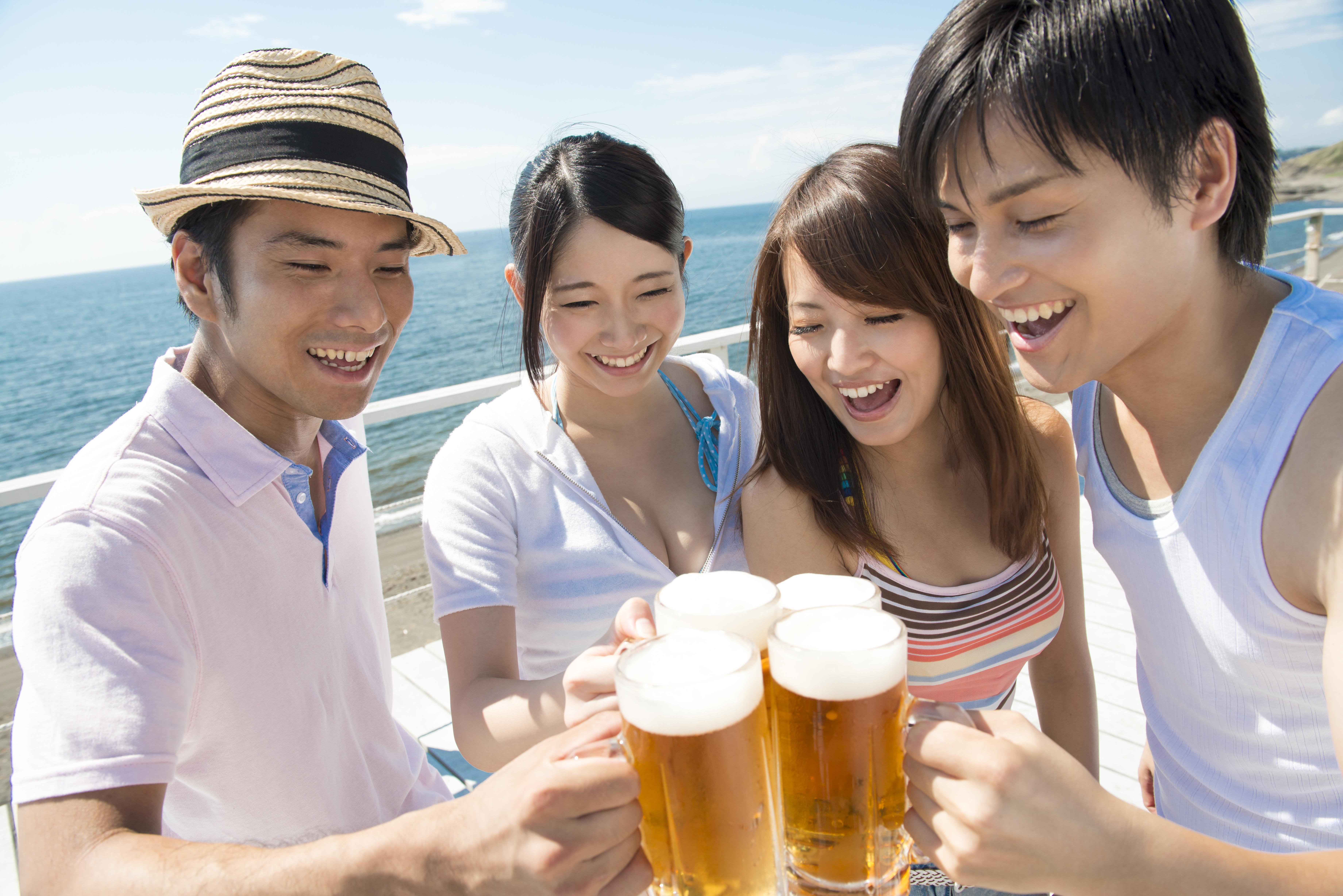 ビールで乾杯している男女のグループ