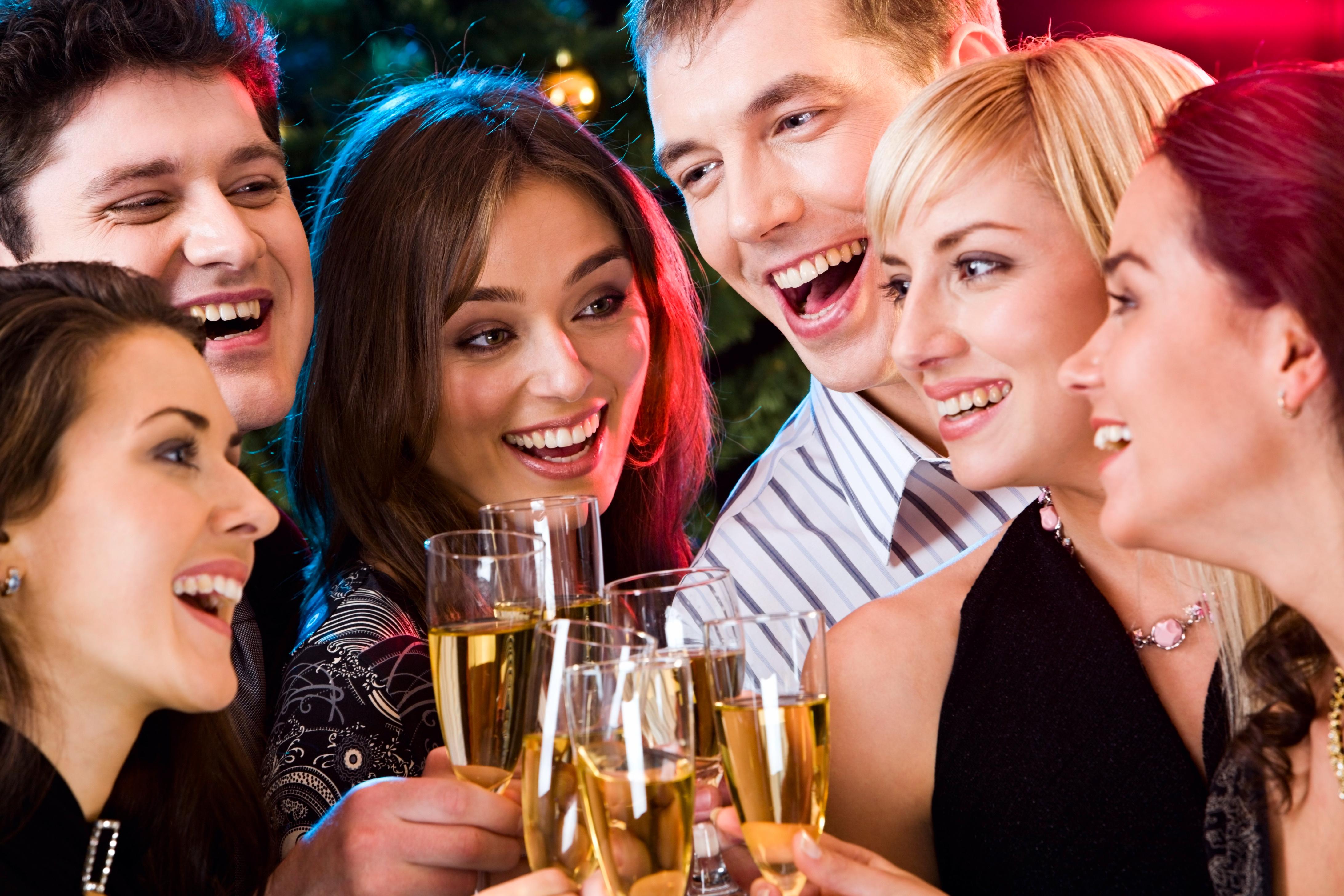 シャンパングラスを片手に乾杯している男女のグループ