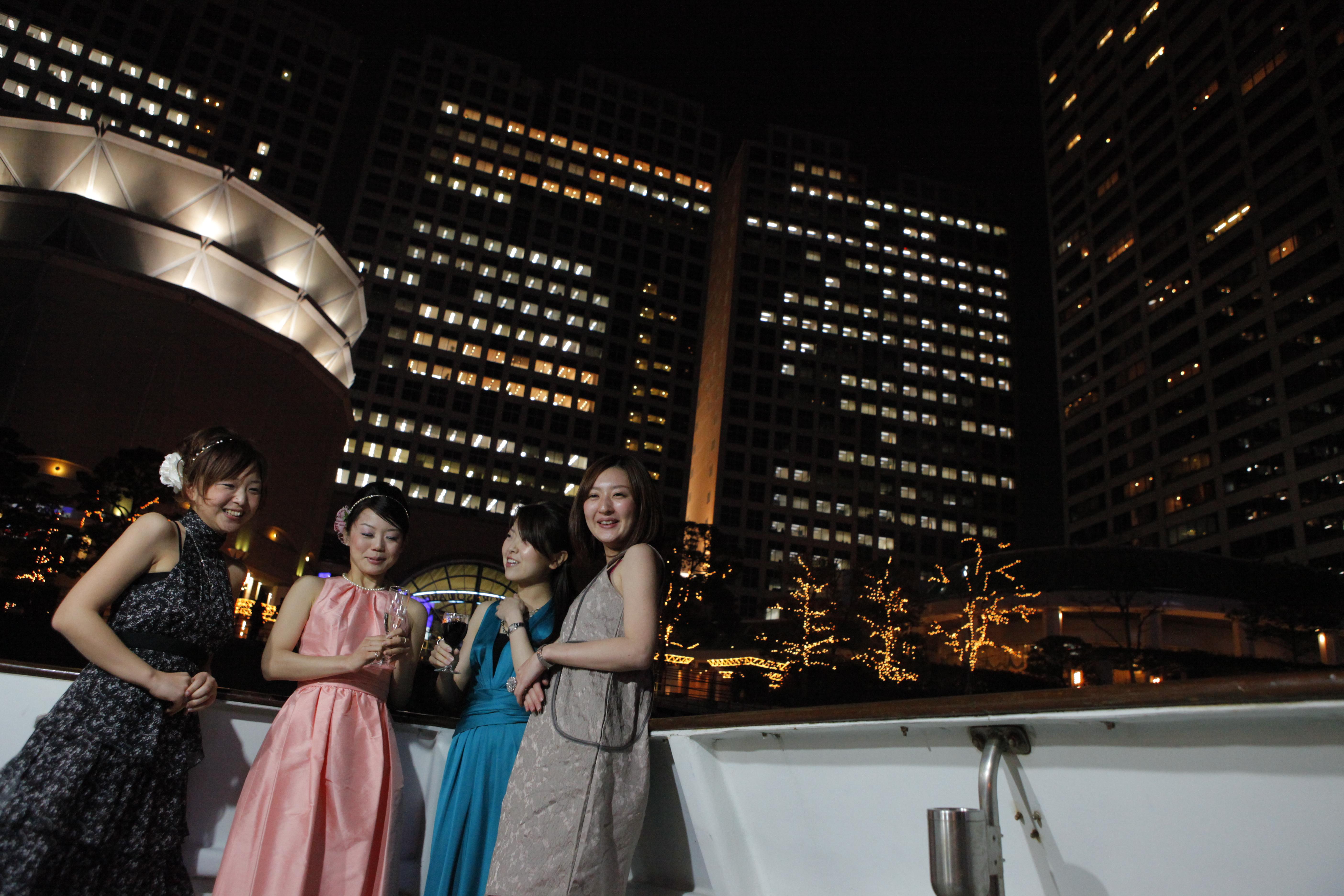 夜景とパーティードレスの女性達