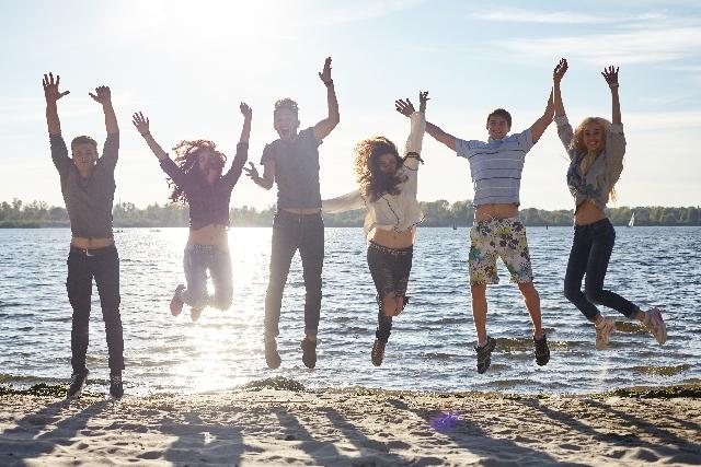 海岸で手をつないで人間六人がジャンプしている