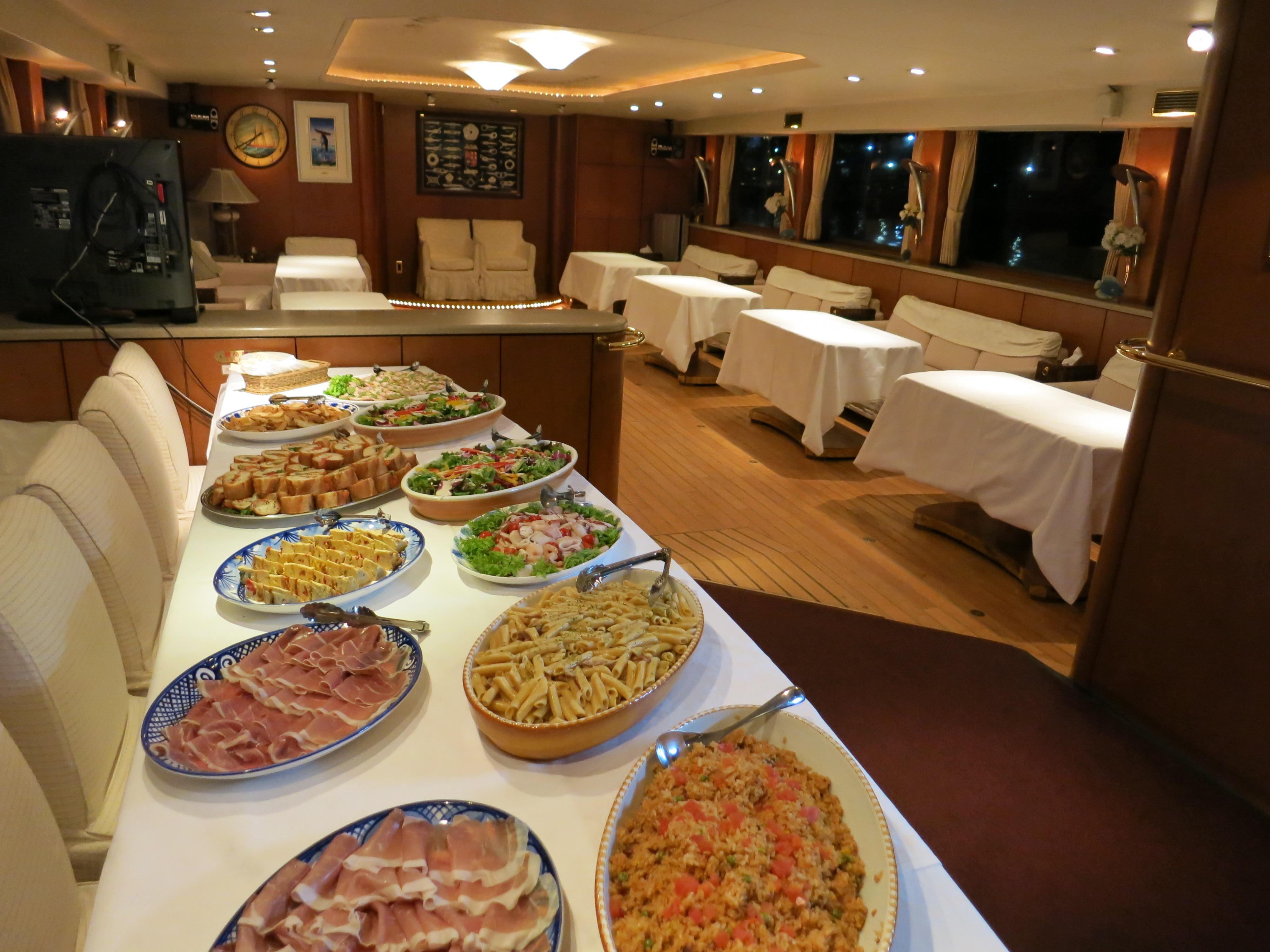 ビュッフェスタイルの料理が並ぶ船内の会場