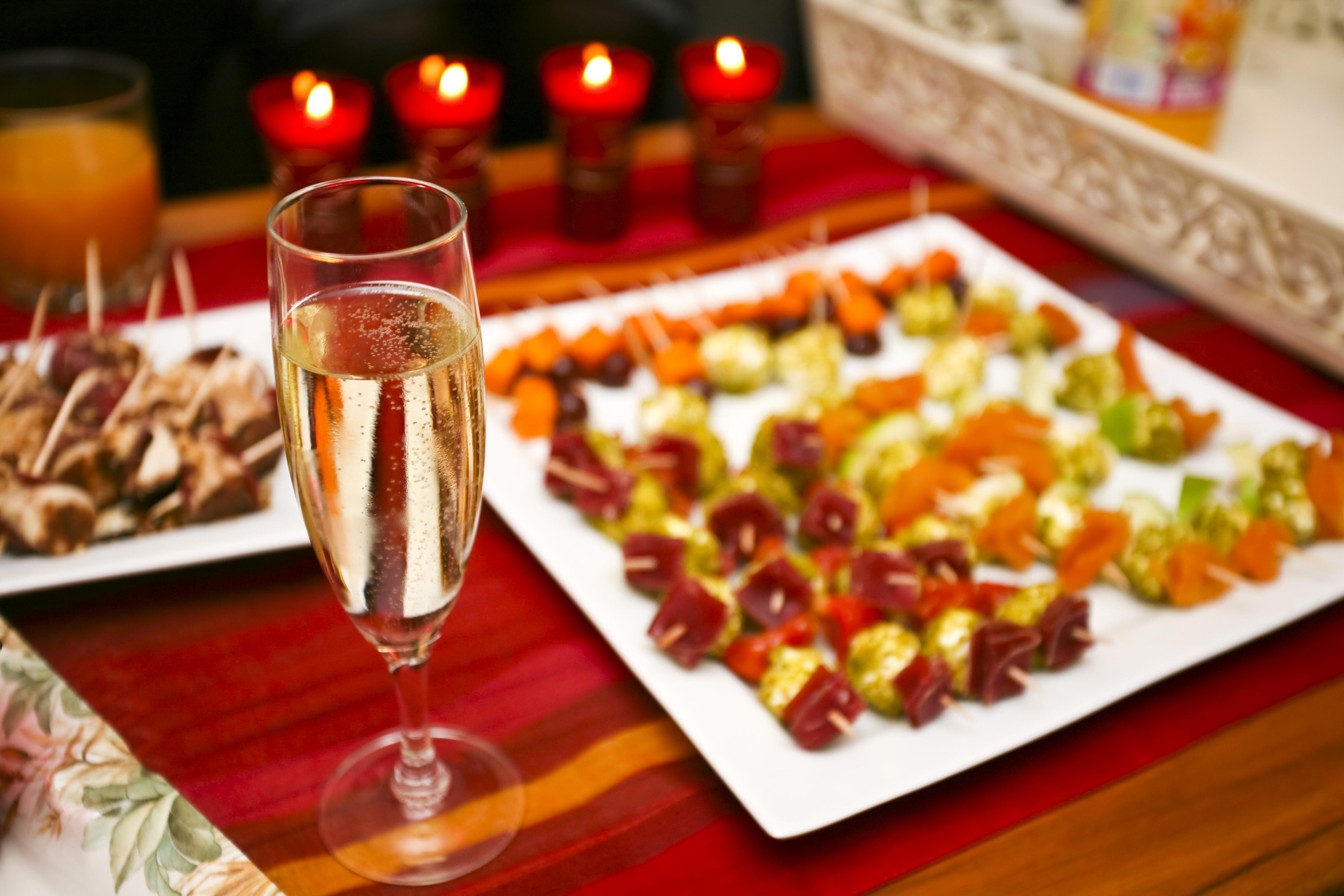 シャンパングラスやビュッフェ料理、キャンドルが並ぶテーブル