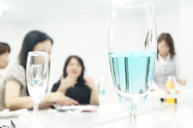 シャンパングラスとその奥に座っている女性たち