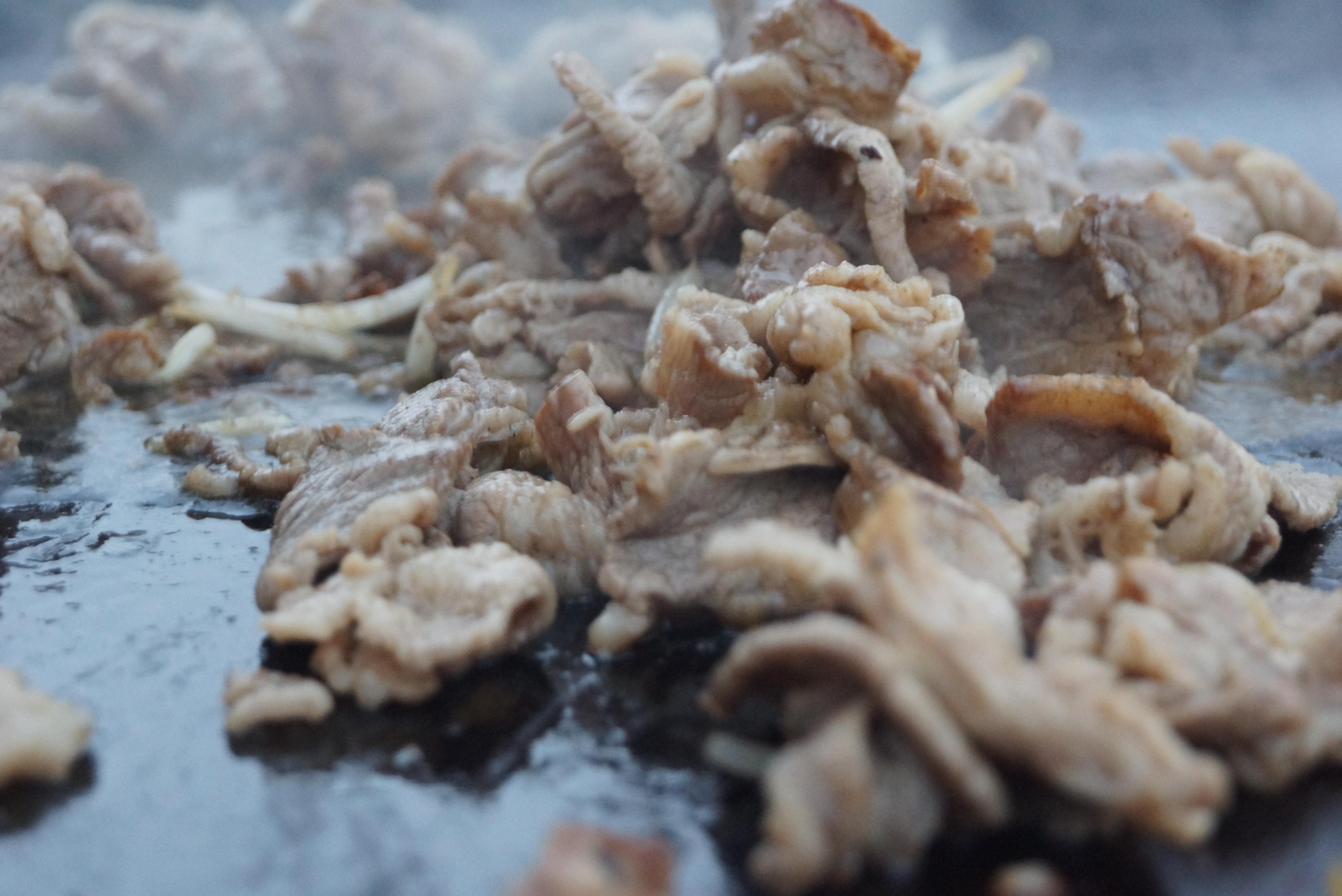 バーベキューの鉄板の上で焼かれている肉
