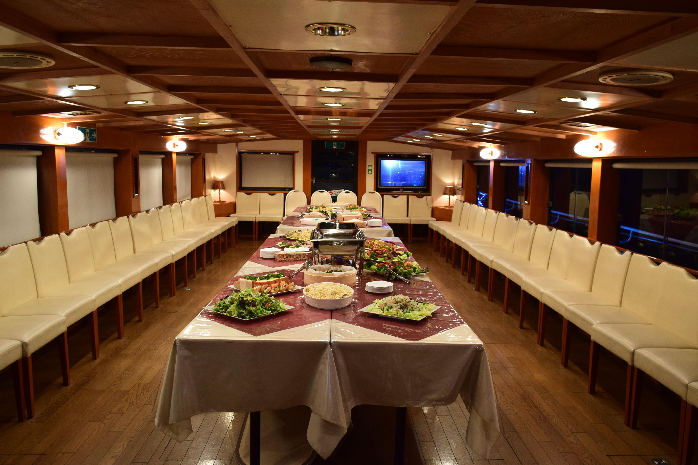 船内の料理が並んだテーブルと並んだイス