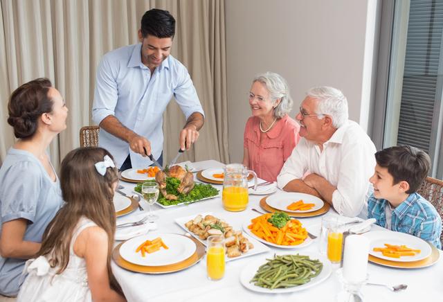 料理が並んだテーブルを囲んで談笑している家族