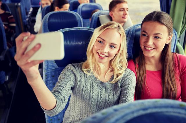 社員旅行のバスの中で自撮りをする女性