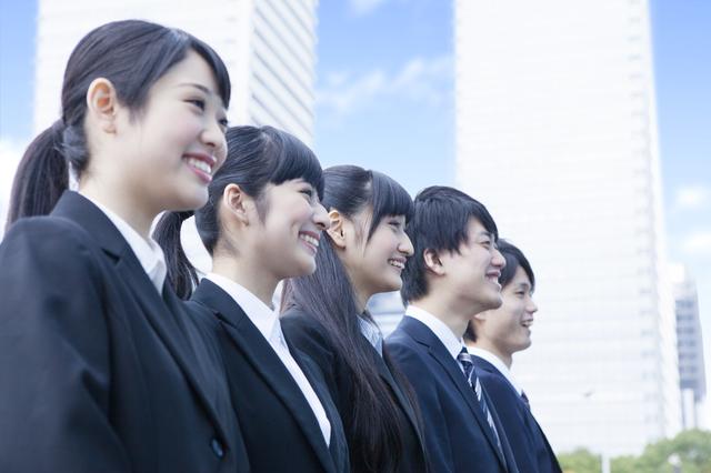 スーツを着て笑顔で並ぶ若い男女のグループ
