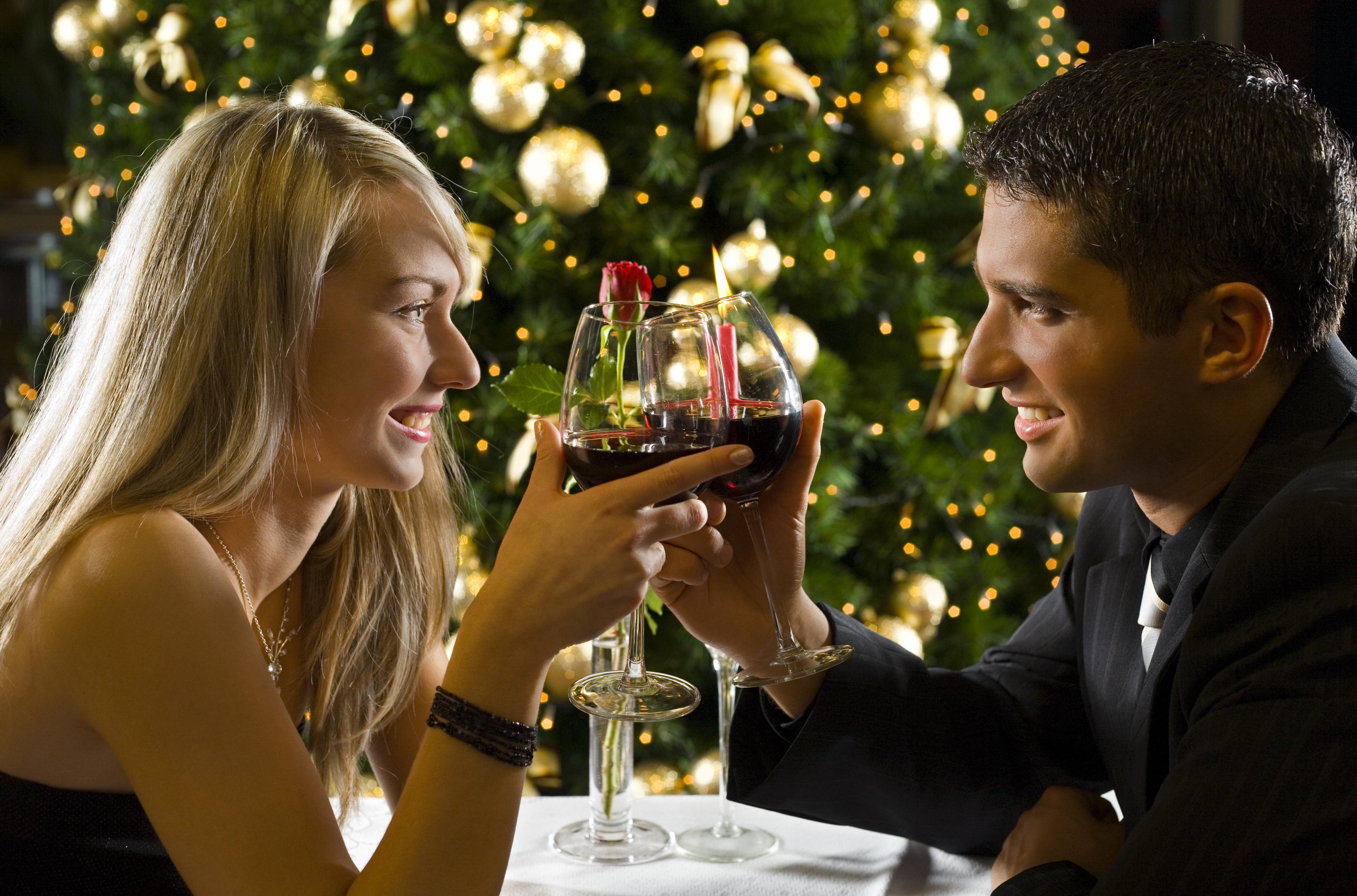 赤ワインが入ったグラスを持って向き合って微笑み合っている男女