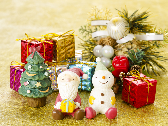 サンタクローズと雪だるまの人形の後ろに小さなクリスマスツリーとプレゼント