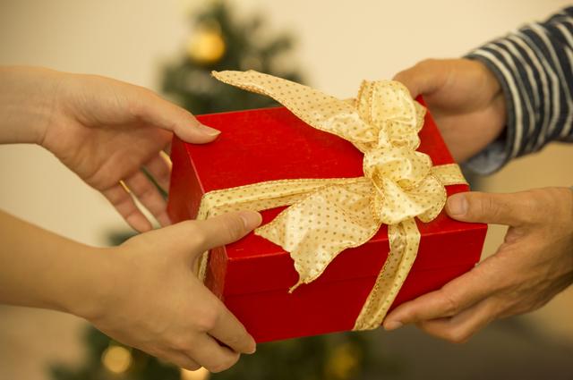 手渡されている赤い箱に金色のリボンがついているプレゼント