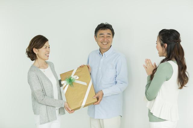両親へプレゼントを渡す女性