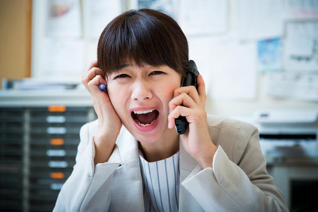 電話をかけながら焦っている女性