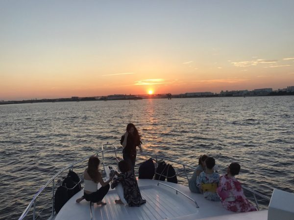 船上から水平線に沈む夕日を眺める風景