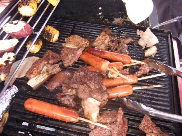 BBQコンロで肉やソーセージ、野菜などを焼いている風景