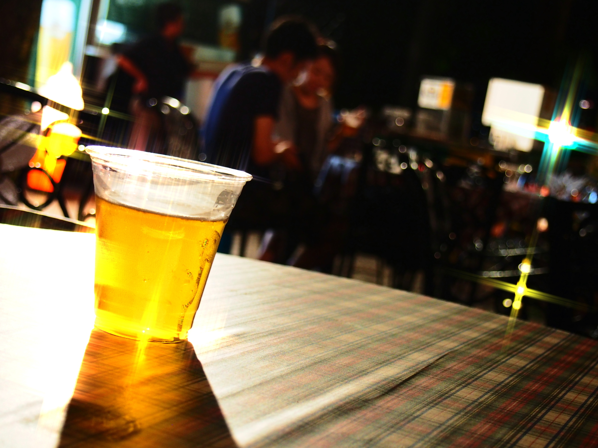 テーブル置かれた透明カップのビールとビアガーデンの風景