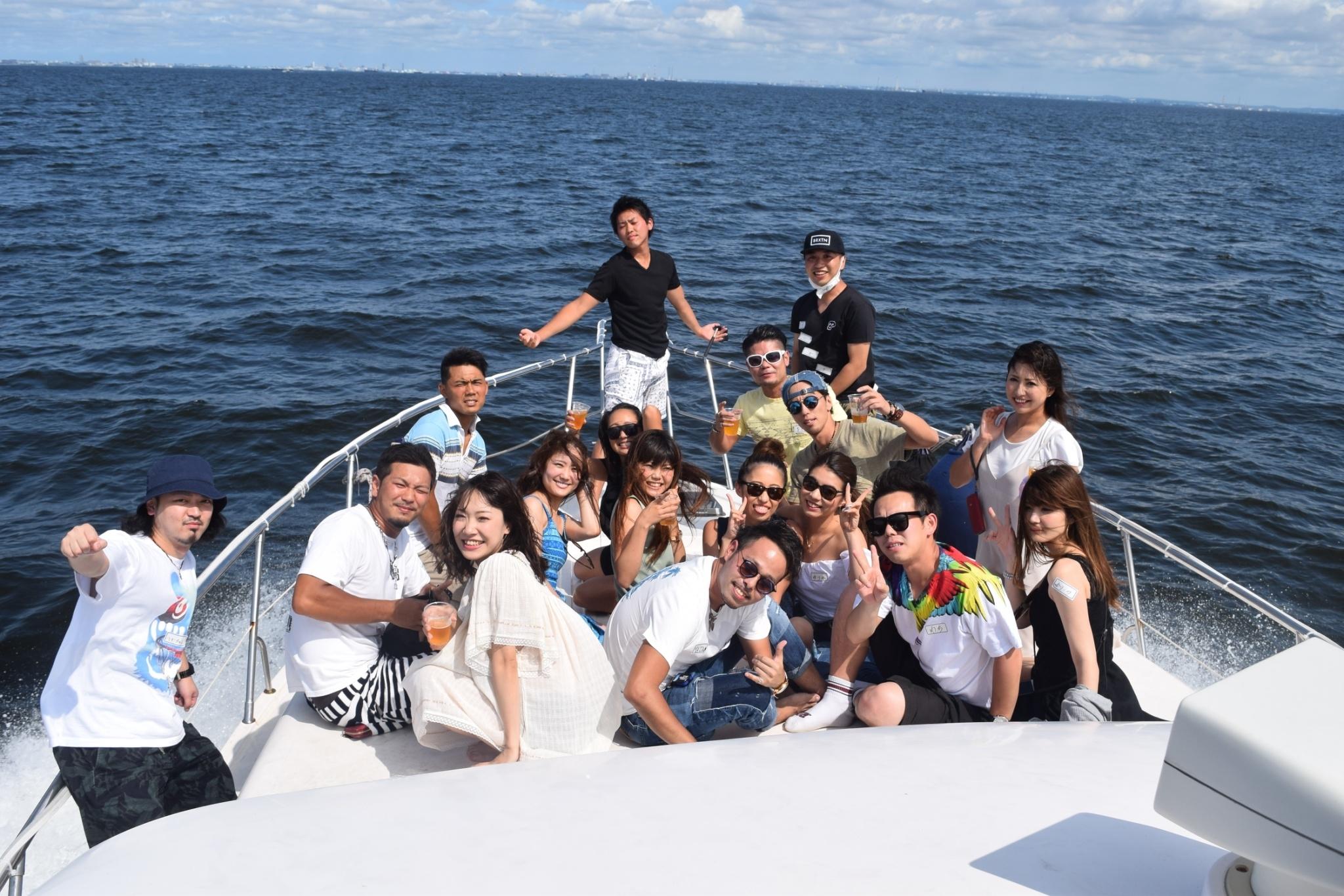 海を背景にしたクルーザー前部デッキでの集合写真