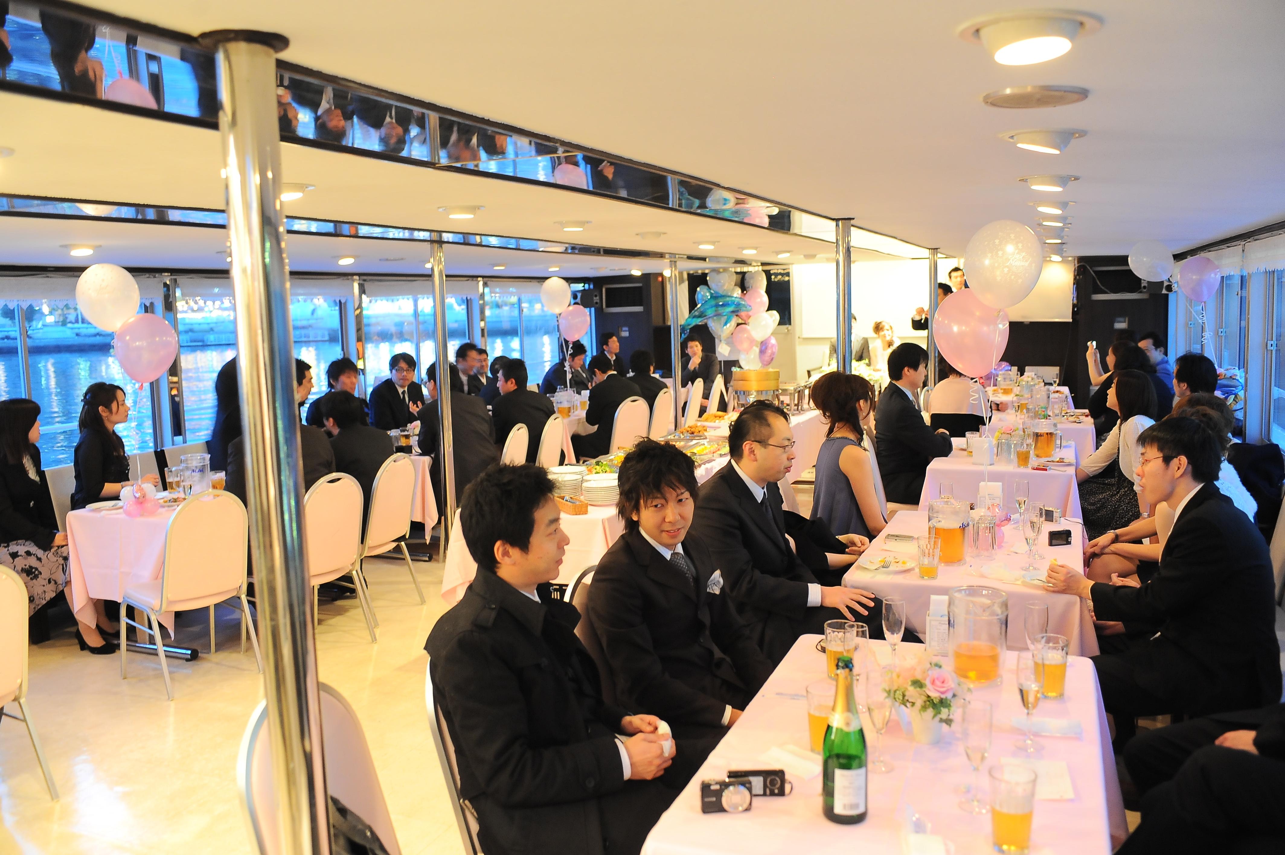 バルーンや卓上花で装飾された船内でパーティーを楽しむ人たち