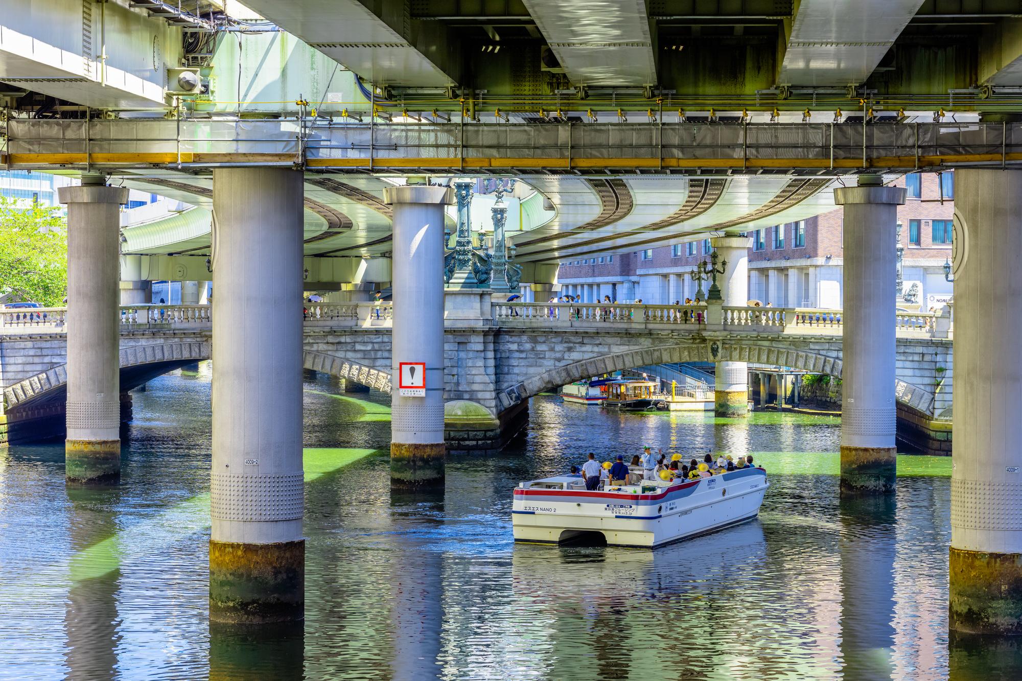 歴史ある橋の下を運航する小さなクルーザー