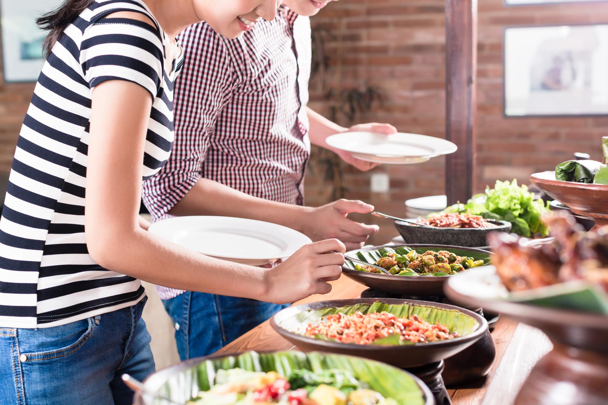 ビュッフェ料理を皿に取る人