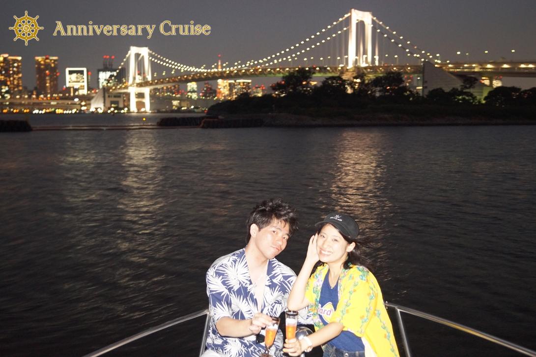 レインボーブリッジの夜景をバックにしたカップルの記念写真
