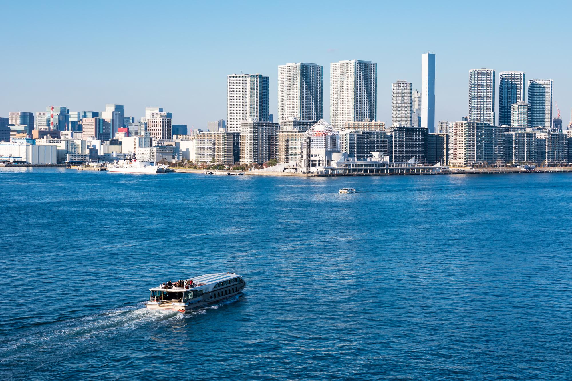 広い海を進むクルーザーと都会の街並み